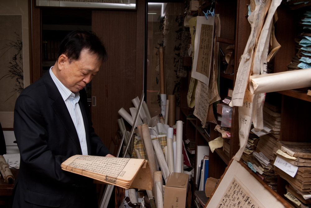 An antique bookshop owner looking at an old manuscript